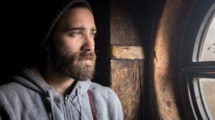 Cristãos Pentecostais Preconceituosos - Imagem de homem com barba olhando ao relento por uma janela antiga