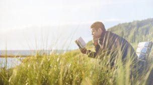 Homem sentando em um banco lendo um livro ao ar livre